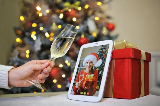 Een meisje heft het glas op haar metgezel die op kerstavond met haar aan het telefoneren is