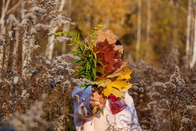 Een meisje houdt een kleurrijk boeket herfstbladeren vast. detailopname.