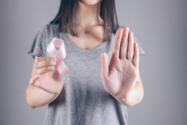 Een meisje houdt een lint met een kanker-teken in haar hand en toont een stopteken met de andere hand
