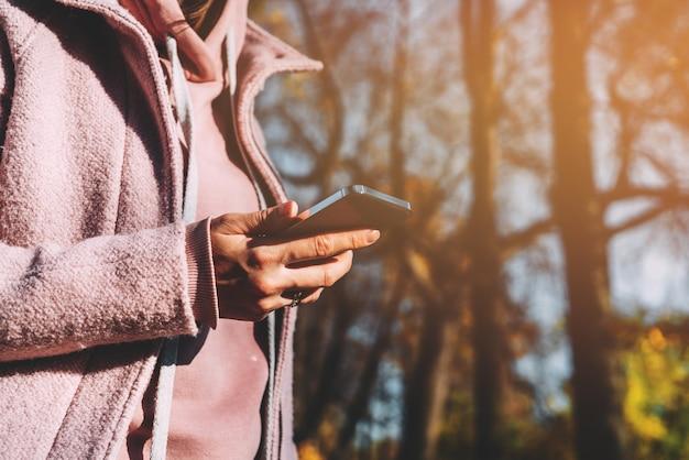 Een meisje houdt een moderne smartphone in haar handen en gebruikt internet.
