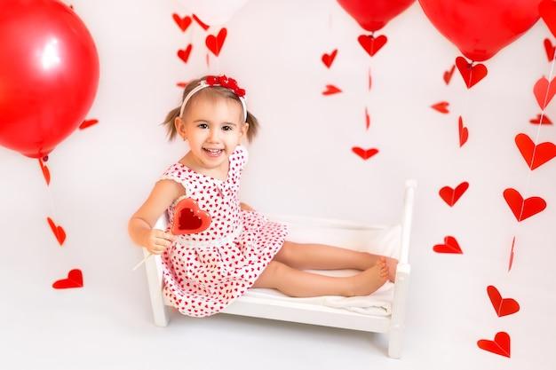 Een meisje houdt een snoepje op een achtergrond van rode ballen en harten.