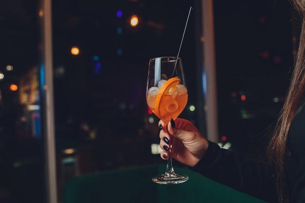 Een meisje houdt in haar hand een transparant glas rode cocktail, ijsblokjes drijven in het glas.