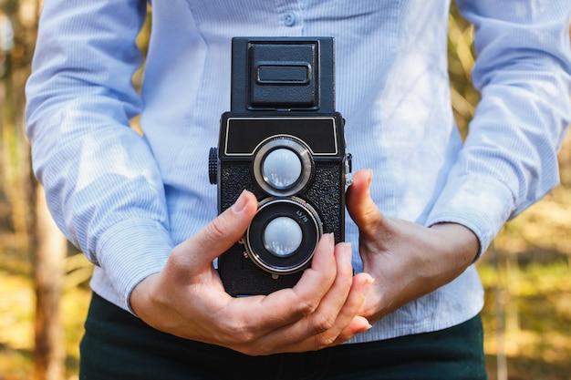 Een meisje houdt in haar handen een oude camera van de filmfoto in het de lentebos