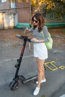 Een meisje huurt een elektrische scooter met een applicatie op haar telefoon. selfservice elektrische scooterverhuur op straat.