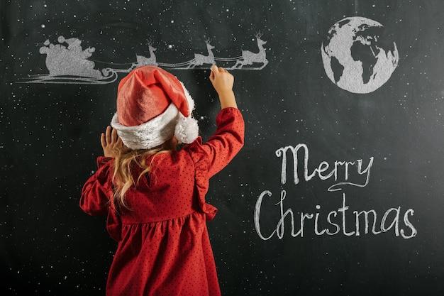 Een meisje in de hoed van de kerstman trekt kersttekening op het bord