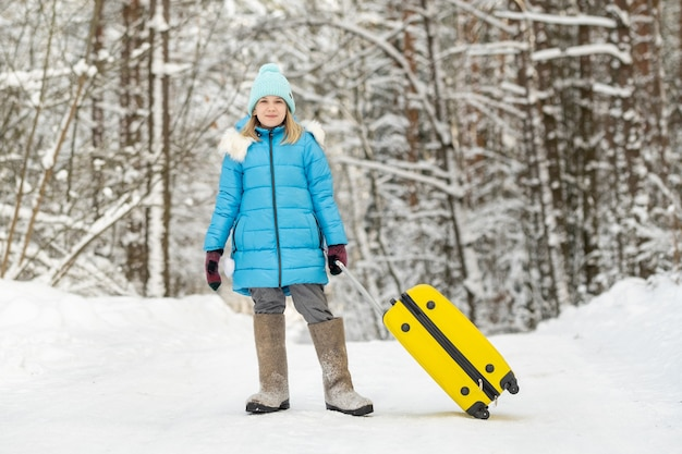 Een meisje in de winter in vilten laarzen gaat met een koffer op een ijzige sneeuwdag.