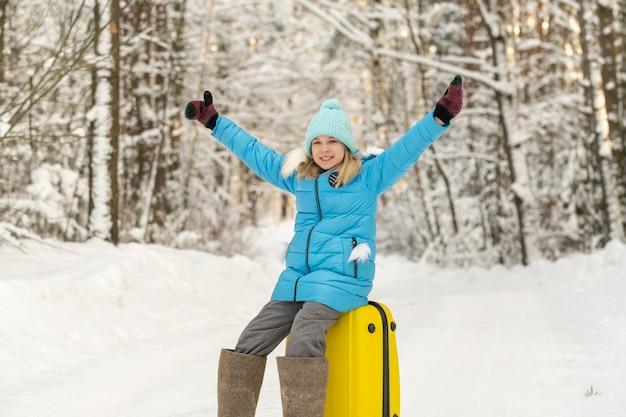 Een meisje in de winter in vilten laarzen zit op een koffer op een ijzige sneeuwdag.