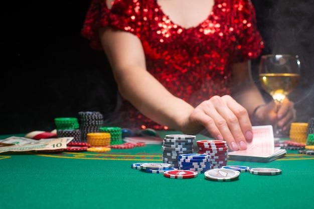 Een meisje in een avond rode jurk speelt in een casino en trekt kaarten