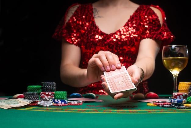 Een meisje in een avond rode jurk speelt in een casino