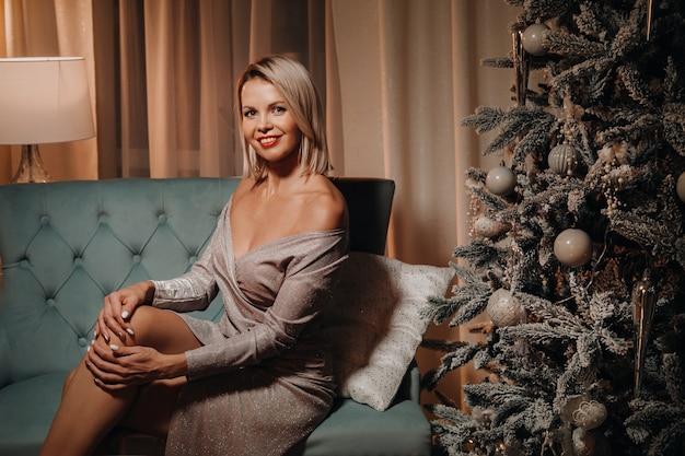 Een meisje in een avondjurk zit op de bank bij de kerstboom.
