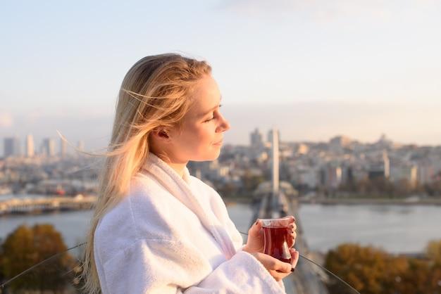 Een meisje in een badjas met een kopje turkse thee bij zonsopgang op het terras van een huis