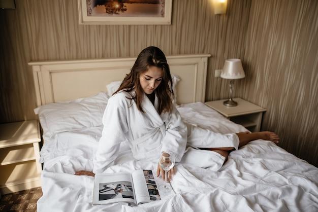 Een meisje in een badjas zittend op een bed een tijdschrift te lezen