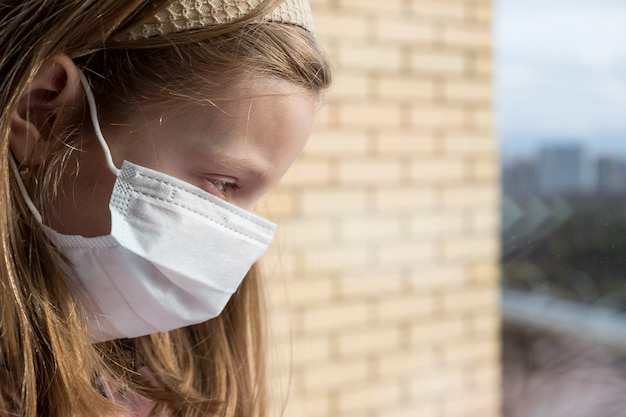 Een meisje in een beschermend masker op haar gezicht. coronavirus. blijf thuis, blijf veilig. quarantaine, pandemische preventie