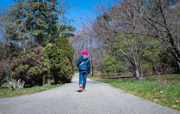 Een meisje in een blauwe jas en een roze hoed loopt op een zonnige lentedag langs het pad in het arboretumpark. sochi, rusland