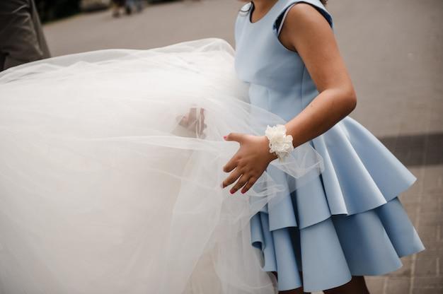 Een meisje in een blauwe jurk draagt een trein van de bruid. witte weelderige trouwjurk. boutonniere aan de kant van verse bloemen. bruiloft details.