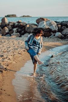 Een meisje in een blauwe jurk loopt langs de kustlijn van het strand. zomer op zee, wandelen bij zonsondergang.
