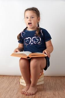 Een meisje in een blauwe spijkerjurk zit op een stapel boeken en houdt een open boek op haar schoot. een gelukkig kind leest en spreekt, geïsoleerd