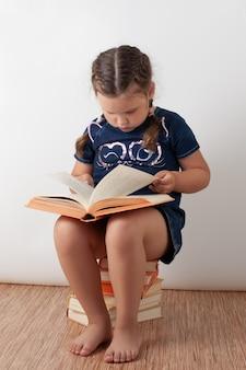 Een meisje in een blauwe spijkerjurk zit op een stapel boeken en houdt een open boek op haar schoot. een gelukkig kind leest, geïsoleerd