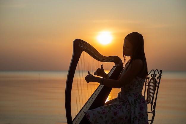 Een meisje in een bloemenjurk speelt op een keltische harp aan zee bij zonsondergang