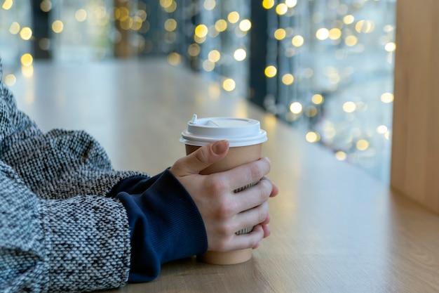 Een meisje in een café houdt een kartonnen beker met koffie in haar handen op een houten tafel tegen de achtergrond