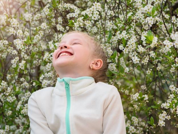 Een meisje in een colbert lacht vrolijk in een lentepark.