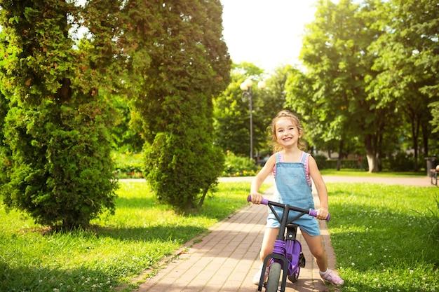 Een meisje in een denim jumpsuit rijdt in de zomer op een paarse hardloopfiets