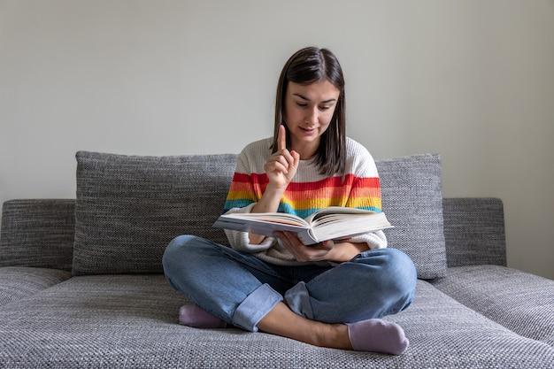Een meisje in een felgekleurde trui leest thuis een boek op de bank.