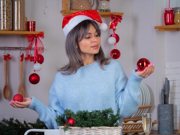 Een meisje in een gebreide trui kiest welk speelgoed de kerstboom zal versieren