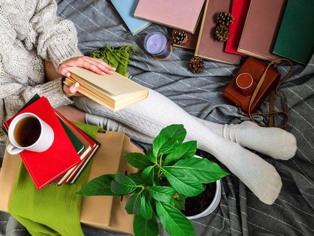 Een meisje in een gebreide trui wordt omringd door veel verschillende oude boeken.