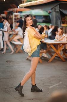 Een meisje in een geel shirt, korte broek en zwarte schoenen met een net van citroenen en citroensap loopt door een stadsstraat