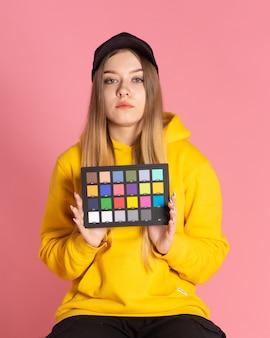 Een meisje in een gele hoodie en een zwarte pet is in de studio met een kleurcontrole in haar handen, de achtergrond achter haar is roze
