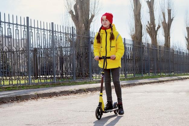 Een meisje in een gele jas rijdt op een scooter op een lege straat. kinderen en ecologisch vervoersconcept.