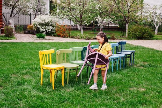 Een meisje in een gele jurk draagt een houten stoel en schikt stoelen in een rij die een kinderfeestje organiseert.