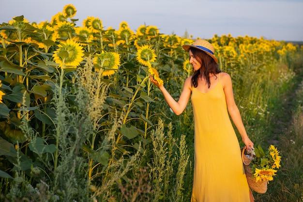 Een meisje in een gele jurk en een strohoed pakt een zonnebloembloem in het midden van een groot veld met zonnebloemen en houdt een boeket zonnebloemen in een strozak. een heerlijke zonnige avond.