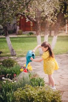 Een meisje in een gele jurk geeft ijverig tulpen water uit een gieter water stroomt uit de wa...