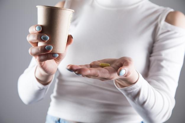 Een meisje in een gele jurk houdt een pil en een glas water vast