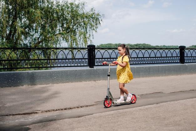 Een meisje in een gele jurk leert op een scooter rijden die ze voor haar verjaardag heeft gekregen langs het stadsmeer