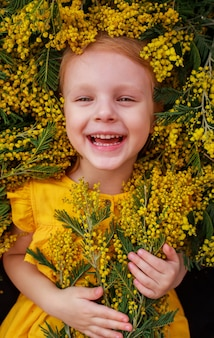 Een meisje in een gele jurk liggend in een veld omringd door gele mismosa-bloemen