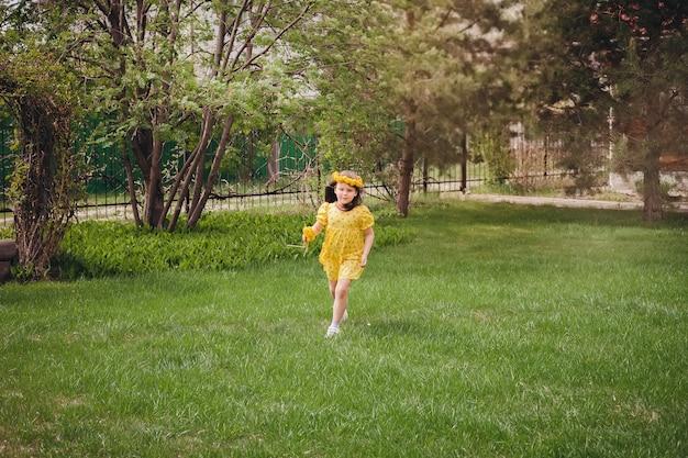 Een meisje in een gele jurk rent op het groene gras en geniet van een zomerse reis met haar familie naar een warme ...