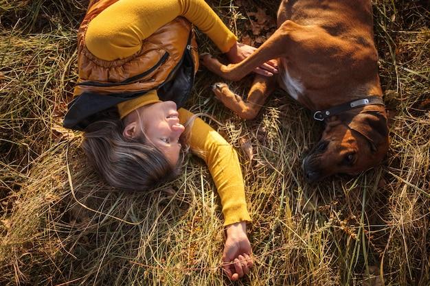 Een meisje in een gele trui en een rhodesian ridgeback liggen samen op het herfstgras