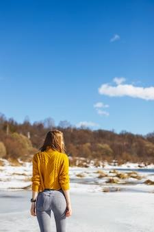 Een meisje in een gele trui met een korte haarsnit staat terug op het ijs van de rivier.