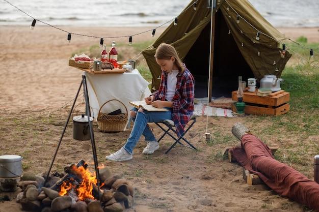 Een meisje in een geruit overhemd en blauwe spijkerbroek leest een boek naast een kampvuur.