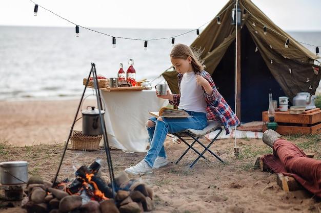 Een meisje in een geruit overhemd leest een boek naast een kampvuur