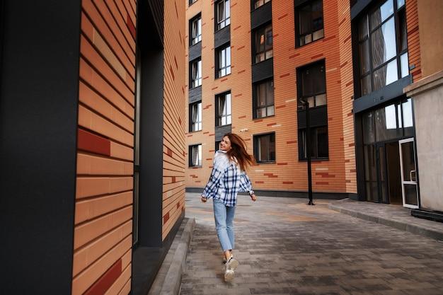 Een meisje in een geruit overhemd rent door de stad en lacht. stedelijke stijl