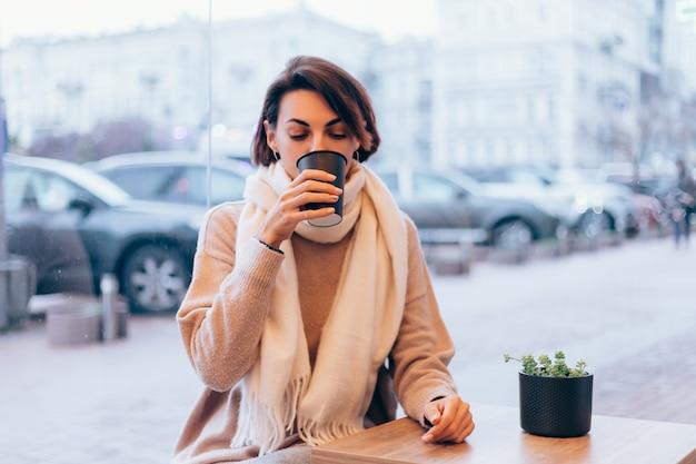 Een meisje in een gezellig café warmt zichzelf op met een kop warme koffie