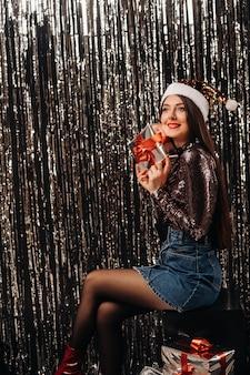 Een meisje in een glanzend jasje met een kerstmuts met geschenken op een zilveren achtergrond in de vorm van regen.