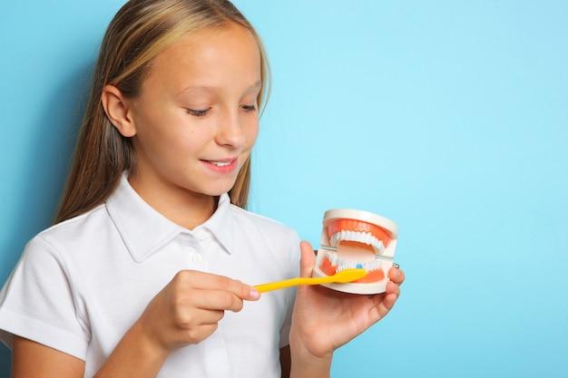 Een meisje in een goed humeur poetst haar tanden en houdt een tandmodel vast
