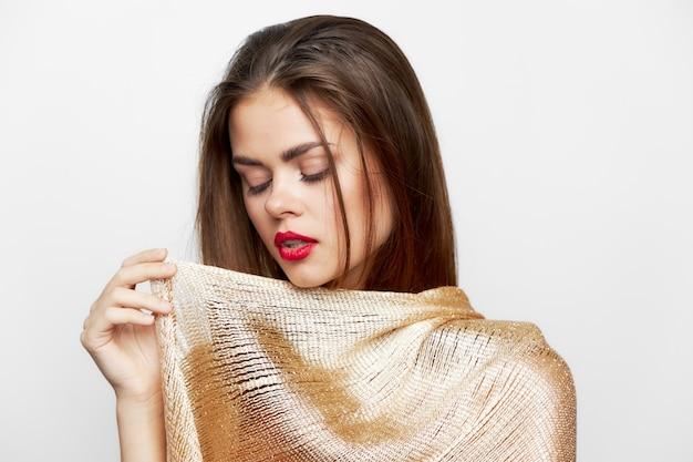 Een meisje in een gouden sjaal ogen gesloten charme model modieuze stijl