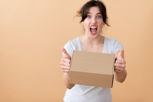 Een meisje in een grijs t-shirt schreeuwt emotioneel met een merkdoos in haar handen en toont haar duimen op een beige ruimte