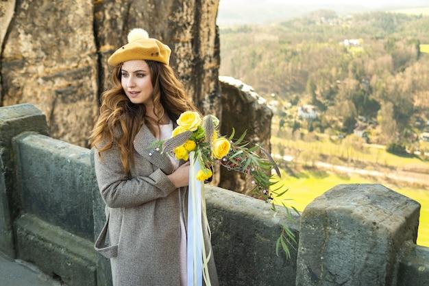 Een meisje in een grijze jas en hoed met een boeket bloemen op de achtergrond van bergen en kloven in zwitsers saksen, duitsland, bastei